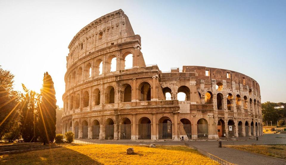 "<p>The origins of the Colosseum date back to 72 A.D., when emperor Vespasian originally commissioned an amphitheater on the grounds of the Domus Aurea complex. Vespasian didn't live to see the project completed, but his son, Titus held games for 100 days and nights to inaugurate the staggering structure. </p><p>It's said that one of those games included a staged <a href=""http://www.bbc.co.uk/history/ancient/romans/colosseum_01.shtml"" rel=""nofollow noopener"" target=""_blank"" data-ylk=""slk:sea battle"" class=""link rapid-noclick-resp"">sea battle</a> where the Colosseum was filled with water so ships could easily move throughout. As archaeologists continue to restore the amphitheater, many believe the decorative hallways, outside arches, and facade were once painted in bright colors.</p>"