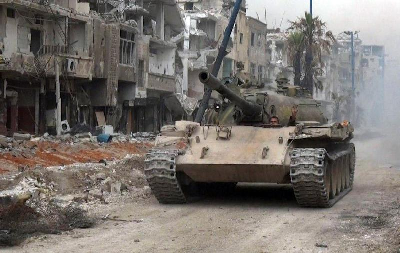 A handout picture released by the official SANA news agency on May 10, 2018 shows a Syrian army tank advancing through a street in Hajar al-Aswad in the push against the Islamic State group