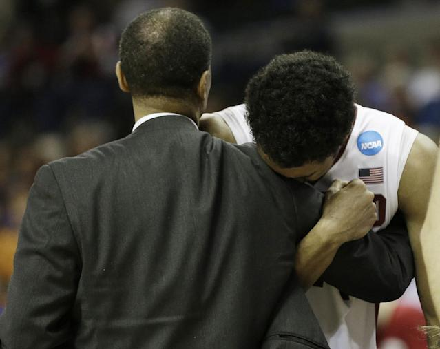 Stanford forward Josh Huestis (24) embraces Stanford head coach Johnny Dawkins after the second half in a regional semifinal game against Dayton at the NCAA college basketball tournament, Thursday, March 27, 2014, in Memphis, Tenn. Dayton won 82-72. (AP Photo/Mark Humphrey)