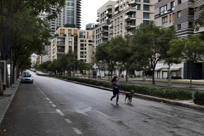 A woman runs with her dog in an almost empty street during a lockdown aimed at curbing the spread of the coronavirus, in Beirut, Lebanon, Thursday, Jan. 14, 2021. Lebanese authorities began enforcing an 11-day nationwide shutdown and round the clock curfew Thursday, hoping to limit the spread of coronavirus infections spinning out of control after the holiday period. (AP Photo/Bilal Hussein)
