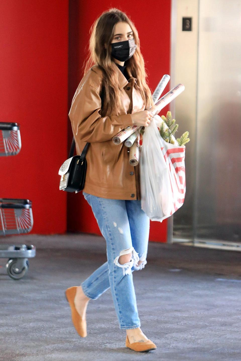 <p>Lily Collins totes her festive finds from a Target in West Hollywood on Saturday.</p>
