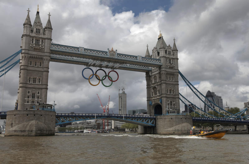 In this photo taken Wednesday, July 4, 2012, a high-speed 12-seater rigid inflatable boat, run by the Protection Services International company, travels past Tower Bridge over London's river Thames, adorned with a huge Olympic rings to honor the games that will take place from July 27-Aug. 12. Companies like Protection Services International are just one of the many catering to the super rich who are coming to the London games and demand top security and easy transport. (AP Photo/Lefteris Pitarakis)