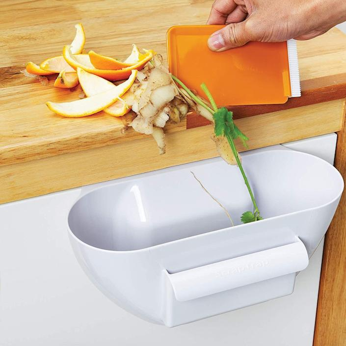 """With this, you can easily wipe away crumbs and bits of food<i>while</i>you're cooking, rather than having to do it later on a full stomach.This also includes a brush/scraper that fits neatly in the front pocket to easily swipe scraps and crumbs into the container.<br /><br /><strong>Promising review:</strong>""""Works just as described.<strong>It is so convenient to push scraps from the counter or cutting board into the scrap trap.</strong>Even though it is too big, place a plastic shopping bag in before you fill it and you will have the scraps bagged when you are done. It keeps things neat when doing prep work. Also bought one as a gift, everyone who cooks should have one."""" —<a href=""""https://www.amazon.com/dp/B001UUGWMY?tag=huffpost-bfsyndication-20&ascsubtag=5834502%2C5%2C46%2Cd%2C0%2C0%2C0%2C962%3A1%3B901%3A2%3B900%3A2%3B974%3A3%3B975%3A2%3B982%3A2%2C16277539%2C0"""" target=""""_blank"""" rel=""""noopener noreferrer"""">SR<br /></a><br /><strong>Get it from Amazon for<a href=""""https://www.amazon.com/dp/B001UUGWMY?tag=huffpost-bfsyndication-20&ascsubtag=5834502%2C5%2C46%2Cd%2C0%2C0%2C0%2C962%3A1%3B901%3A2%3B900%3A2%3B974%3A3%3B975%3A2%3B982%3A2%2C16277539%2C0"""" target=""""_blank"""" rel=""""noopener noreferrer"""">$12.99</a>.</strong>"""
