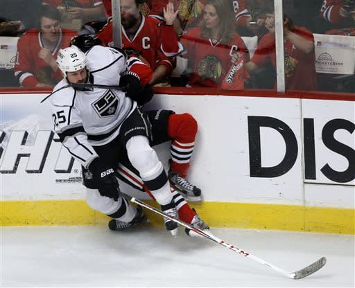 Los Angeles Kings left wing Dustin Penner (25) and Chicago Blackhawks center Marcus Kruger (16) collide during the first period in Game 5 of the NHL hockey Stanley Cup playoffs Western Conference finals Saturday, June 8, 2013, in Chicago. (AP Photo/Charles Rex Arbogast)