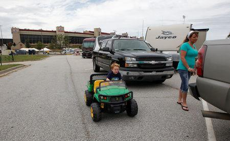 Four year old Brayden Screen rides his toy tractor as his grandmother Stephanie Giordano stands at their trailer after originally driving from Savannah, Georgia to ride out Hurricane Irma at Atlanta Motor Speedway in Hampton, Georgia, U.S., September 10, 2017.  REUTERS/Tami Chappell
