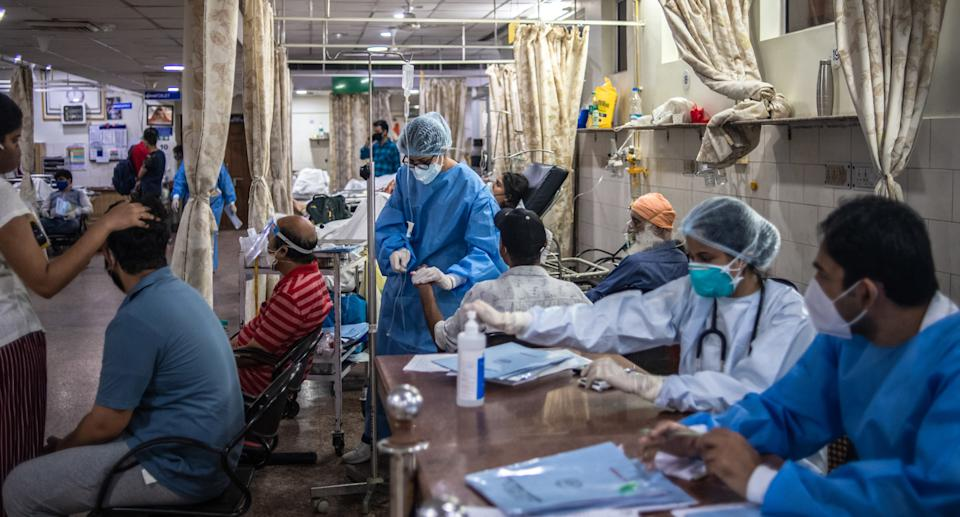 Inside a Covid hospital in India showing beds full and patients sitting up with masks on and health workers nearby.