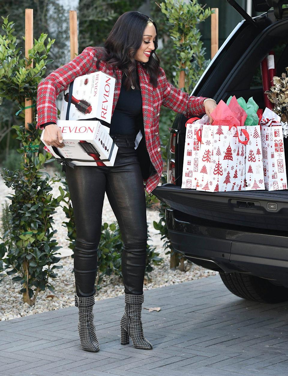 <p>Tia Mowry stocks up on Revlon One-Step Volumizers while holiday shopping on Tuesday in L.A. </p>