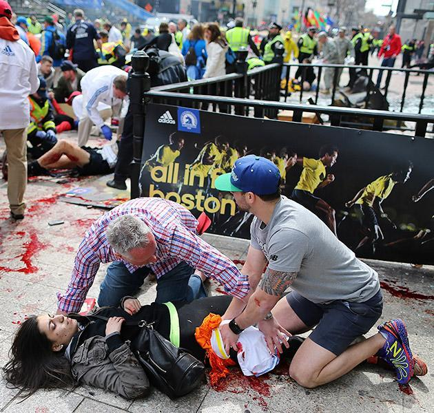 Bystanders help an injured woman at the scene of the first explosion on Boylston Street near the finish line of the 117th Boston Marathon. (Photo by John Tlumacki/The Boston Globe via Getty Images)