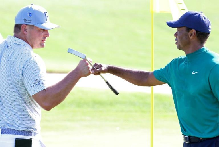 US Open winner Bryson DeChambeau, left, bumps fists with reigning Masters champion Tiger Woods, hoping the 15-time major winner will be placing a green jacket around his shoulders on Sunday at the Masters