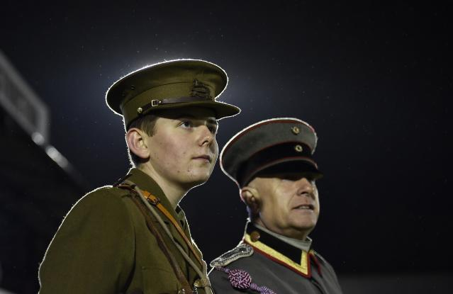 Two men wearing replica World War I British and German army uniforms watch a soccer match between the British Army and German Bundeswehr at Aldershot Town FC stadium in Aldershot in south England, December 17, 2014. The two teams were playing each other in a 'Game of Truce' soccer match, commemorating 100 years since the famous peaceful interlude to fighting in World War I when members of the opposing British and German forces played a game of soccer in No Man's Land on Christmas Day 1914. REUTERS/Toby Melville (BRITAIN - Tags: SPORT SOCCER POLITICS ANNIVERSARY CONFLICT MILITARY)