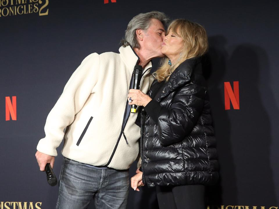 """Kurt Russell gives Goldie Hawn a smooch at Netflix's """"The Christmas Chronicles: Part Two"""" drive-in event in Los Angeles."""