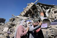Palestinian women pose for a picture in front of a demolished building in Gaza City, recently targeted by Israeli air strikes