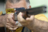 """FILE - In this Feb. 24, 2021 file photo, Owner Eduardo Barzana practices at a shooting range in Americana, Brazil. """"Guns are like cellphones; it's the person behind them who matters,"""" said Barzana. """"What the government is doing is benefiting our sport and giving average citizens the right to defend themselves."""" (AP Photo/Andre Penner, File)"""