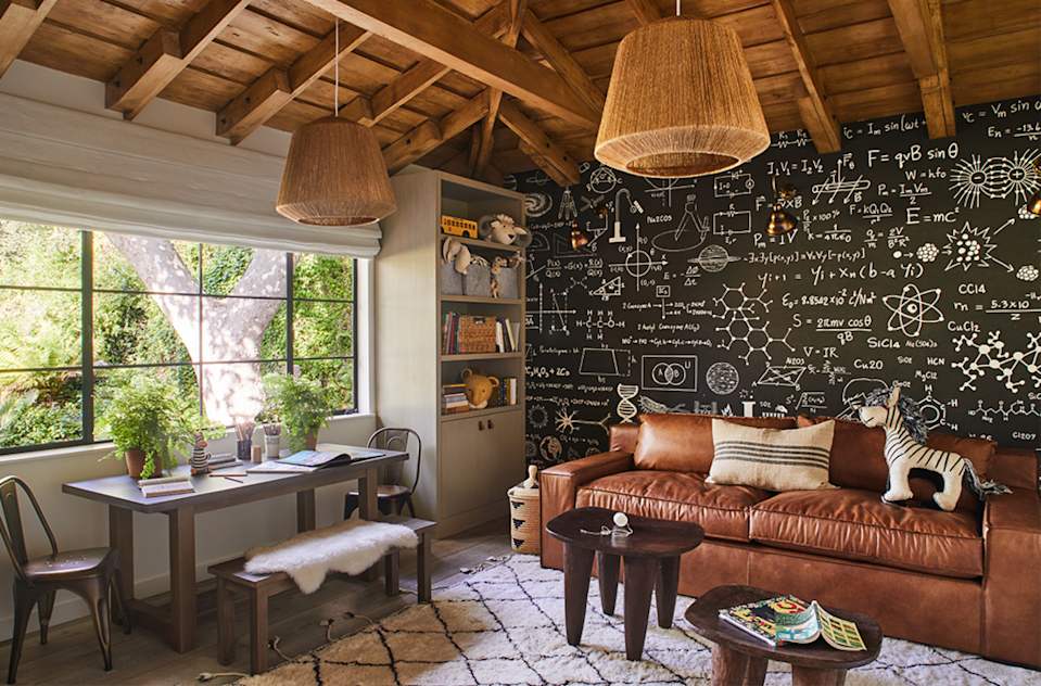 "<p>Opt for a chalkboard wallpaper so the kids can write on the walls without you have to tear them down. It's a fun interactive design element that'll cultivate memories and inspire personal expression. Then choose grownup staples, like a leather sofa, woven pendants, and wooden side tables as seen in this <a href=""https://studio-lifestyle.com/pages/splash"" rel=""nofollow noopener"" target=""_blank"" data-ylk=""slk:Studio Lifestyle"" class=""link rapid-noclick-resp"">Studio Lifestyle</a> space. </p>"