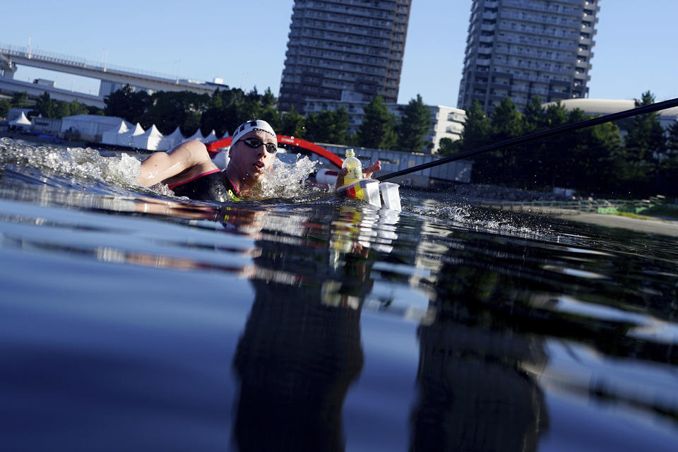 Florian Wellbrock, of Germany, stops for a drink at a feeding station during the men's marathon swimming event at the 2020 Summer Olympics, Thursday, Aug. 5, 2021, in Tokyo. (AP Photo/David Goldman)