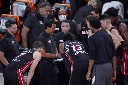 Miami Heat head coach Erik Spoelstra, center left, draws up a play during a time out late in the second half of an NBA conference final playoff basketball game against the Boston Celtics on Saturday, Sept. 19, 2020, in Lake Buena Vista, Fla. (AP Photo/Mark J. Terrill)