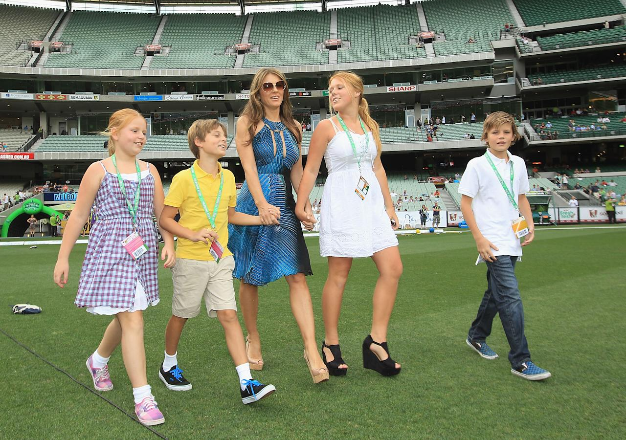 MELBOURNE, AUSTRALIA - DECEMBER 17:  Liz Hurley walks out to toss the coin with her son Damian (yellow) and Shane Warne's children Brooke, Summer (left) and Jackson ahead of the T20 Big Bash League match between the Melbourne Stars and the Sydney Thunder at Melbourne Cricket Ground on December 17, 2011 in Melbourne, Australia.  (Photo by Hamish Blair/Getty Images)