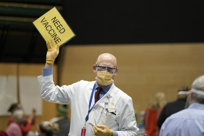 """Dr. John Corman, the chief clinical officer for Virginia Mason Franciscan Health, holds a sign that reads """"Need Vaccine"""" to signal workers to bring him more doses of the Pfizer vaccine for COVID-19, Sunday, Jan. 24, 2021, as he works at a one-day vaccination clinic set up in an Amazon.com facility in Seattle. (AP Photo/Ted S. Warren)"""