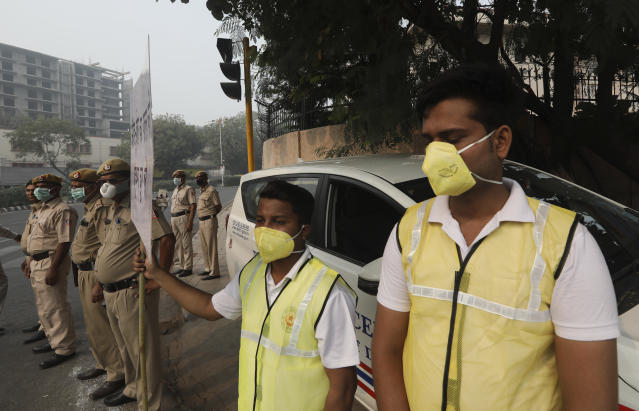 Volunteers and policemen wear pollution masks and stand at a busy crossing with the banner saying obey odd and even, remove pollution, in New Delhi, India, Nov. 4, 2019. (Photo: Manish Swarup/AP)