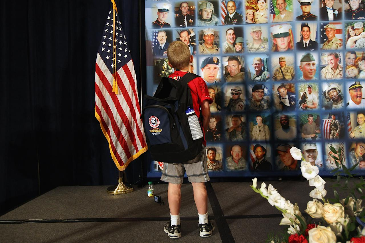 "A child looks over portraits of fallen military personel while participating in the TAPS ""Good Grief Camp"" on May 27, 2012 in Washington, DC. Five hundred military children and teens, many of whom had a parent that was killed in the Afghan and Iraq wars, attended the annual four-day ""Good Grief Camp"" in Arlington, VA and Washington, DC, which is run by TAPS (Tragedy Assistance Program for Survivors). The camp helped them learn coping skills and build relationships so they know they are not alone in the grief of their loved one. They met others of their own age group, learned together and shared their feelings, both through group activities and one-on-one mentors, who are all active duty or former military servicemembers. Some 1,200 adults, most of whom are grieving parents and spouses, also attend the National Military Survival Seminar held concurrently with the children's camp. The TAPS slogan is ""Remember the Love. Celebrate the Life. Share the Journey.""  (Photo by John Moore/Getty Images)"