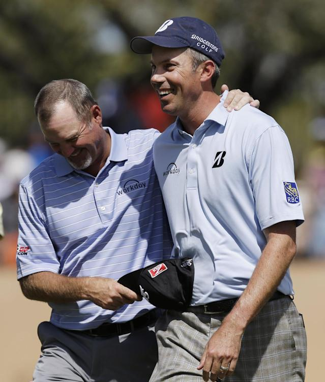 Matt Kuchar, right, walks off the 18th green with playing partner Jerry Kelly, left, after they both birdied the hole during the third round of the Texas Open golf tournament, Saturday, March 29, 2014, in San Antonio. (AP Photo/Eric Gay)