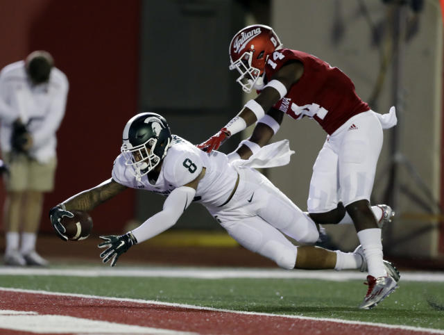 Michigan State wide receiver Jalen Nailor dives in for a touchdown against Indiana's Andre Brown Jr. during the first half of an NCAA college football game, Saturday, Sept. 22, 2018, in Bloomington, Ind. (AP Photo/Darron Cummings)