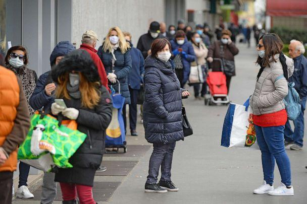 PHOTO: Customers wearing face masks queue at the entrance of a supermarket in Sesto San Giovanni, Milan, Italy, March 23, 2020. (Sergio Pontoriero/EPA via Shutterstock)