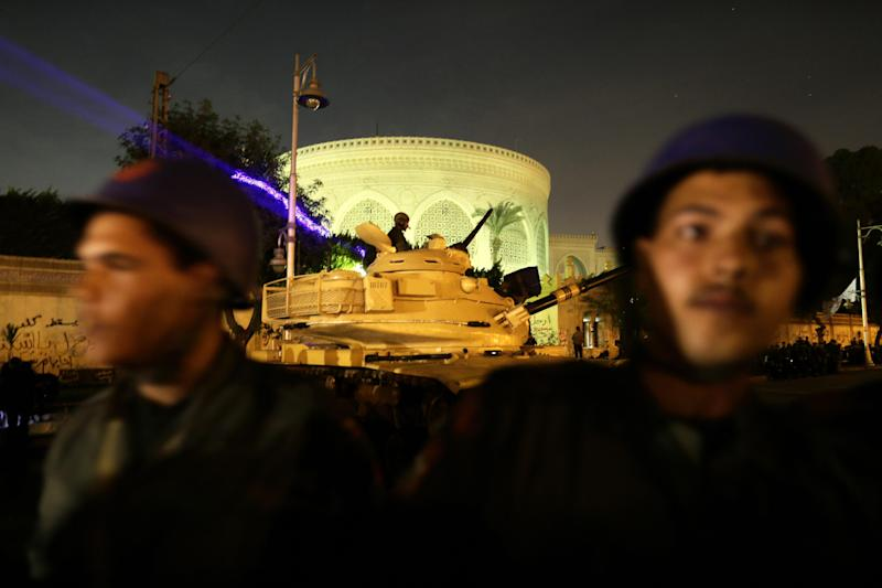 Egyptian army soldiers stand guard as protesters gather in front of the presidential palace during a demonstration against President Mohammed Morsi, in Cairo, Egypt, Tuesday, Dec. 11, 2012. Thousands of opponents and supporters of Egypt's Islamist president staged rival rallies in the nation's capital Tuesday, four days ahead a nationwide referendum on a contentious draft constitution. (AP Photo/Hassan Ammar)