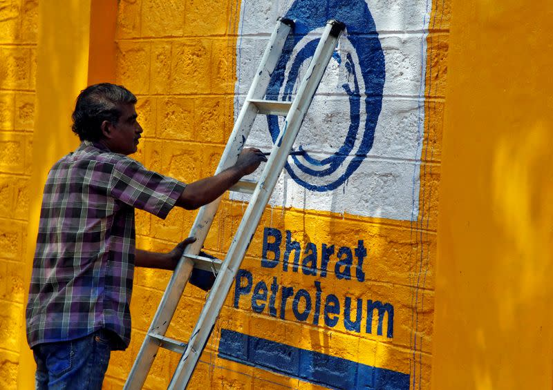 A man paints the logo of oil refiner Bharat Petroleum Corp on a wall on the outskirts of Kochi