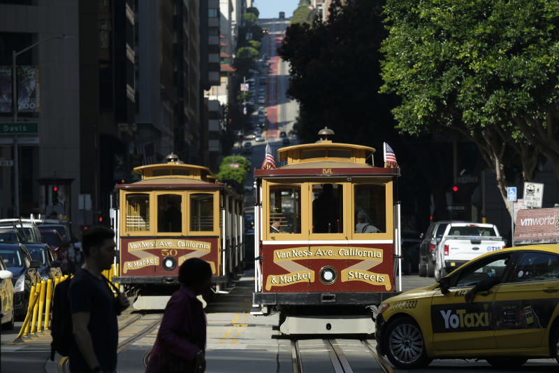 A cable car at right begins to make its way up California Street Wednesday, Sept. 11, 2019, in San Francisco. San Francisco's iconic cable cars will stop running for 10 days starting Friday to undergo repairs. The city's transit agency says it needs to get the manually operated cable cars off the street to rehabilitate the gearboxes that power the system that started in the 1890s. Shuttle buses will instead transport people along the steep streets of the cable car routes. (AP Photo/Eric Risberg)