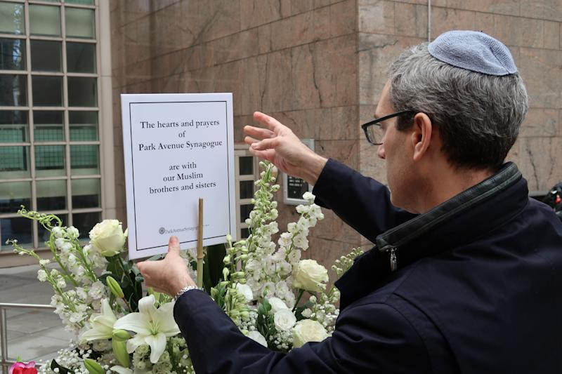 "A man places a support message reading, ""The hearts and prayers of Park Avenue Synagogue are with our Muslim brothers and sisters"" in front of the Islamic Cultural Center in New York, New York."