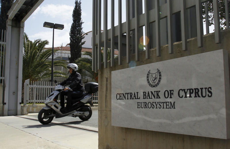 A man on a scooter, exist from a gate of Central Bank of Cyprus in Nicosia, Cyprus, Tuesday, March 13, 2012. International ratings agency Moody's downgraded euro member Cyprus into junk status Tuesday on heightened concerns over the exposure of its large banking sector to Greece. The agency reduced its rating on Cyprus by one notch to Ba1 and assigned a negative outlook, meaning that further downgrades are possible. (AP Photo/Petros Karadjias)