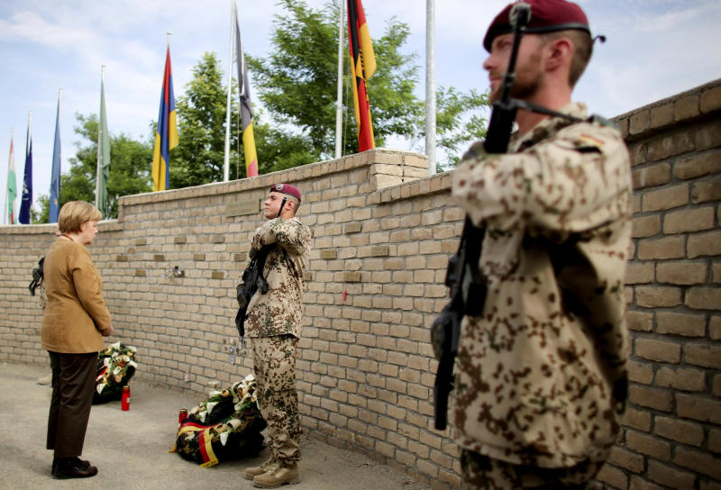 German Chancellor Angela Merkel, left, pauses in front a memorial wall for fallen German soldiers after laying a wreath at the German base in Kunduz, Afghanistan, Friday, May 10, 2013. Germany's Chancellor Angela Merkel made a surprise trip to northern Afghanistan to visit her troops less than two weeks after insurgents killed a German special forces soldier and wounded a second, a military spokesman said. Germany is the only NATO nation that is committed to leaving troops in Afghanistan after the coalition completes its scheduled pullout of combat forces next year. The U.S. is likely to deploy several thousand troops if the Afghan government provides them legal protection. (AP Photo/DPA/Kay Nietfeld)