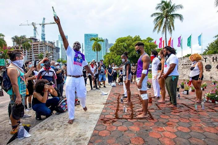 """Little Haiti resident and Voudou Priest Ovida Alva, 49, sprays the crowd and demonstrators with a concoction of alcohol and fragrances during a """"Say Their Names"""" protest at The Torch of Friendship in Miami, Florida on Saturday, July 4."""