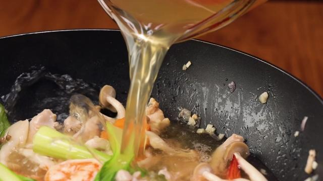 Pouring chicken stock into a pan of stir fried ingredients