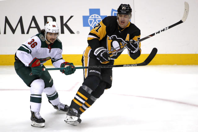 Pittsburgh Penguins' Evgeni Malkin (71) is defended by Minnesota Wild's Mats Zuccarello (36) during the first period of an NHL hockey game in Pittsburgh, Tuesday, Jan. 14, 2020. (AP Photo/Gene J. Puskar)