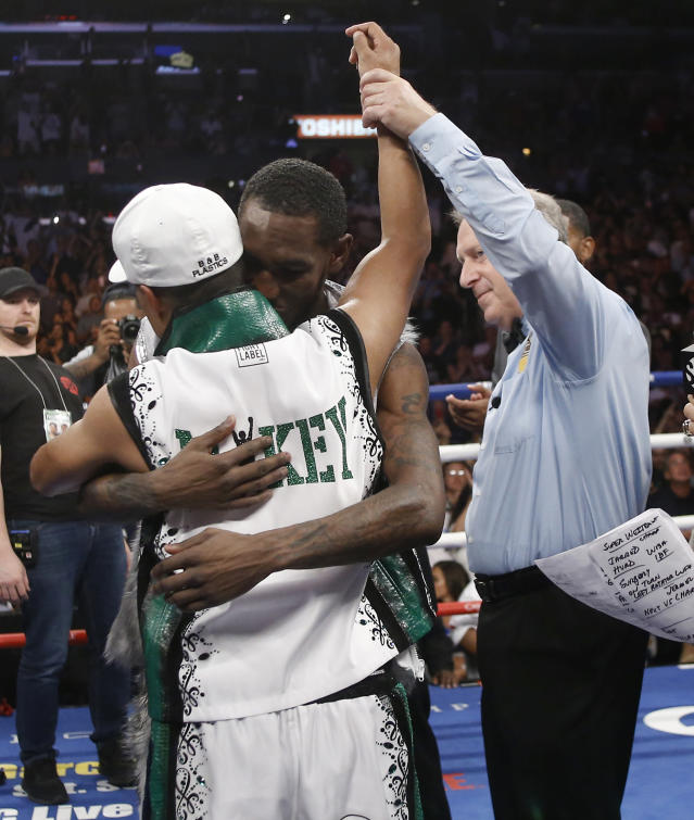 Judge Jack Reiss, right, holds up Mikey Garcia's arm, as Robert Easter Jr., center, hugs Garcia in congratulations, after a unanimous decision is announced in their WBC and IBF lightweight title bout in Los Angeles, Saturday, July 28, 2018. (AP Photo/Alex Gallardo)