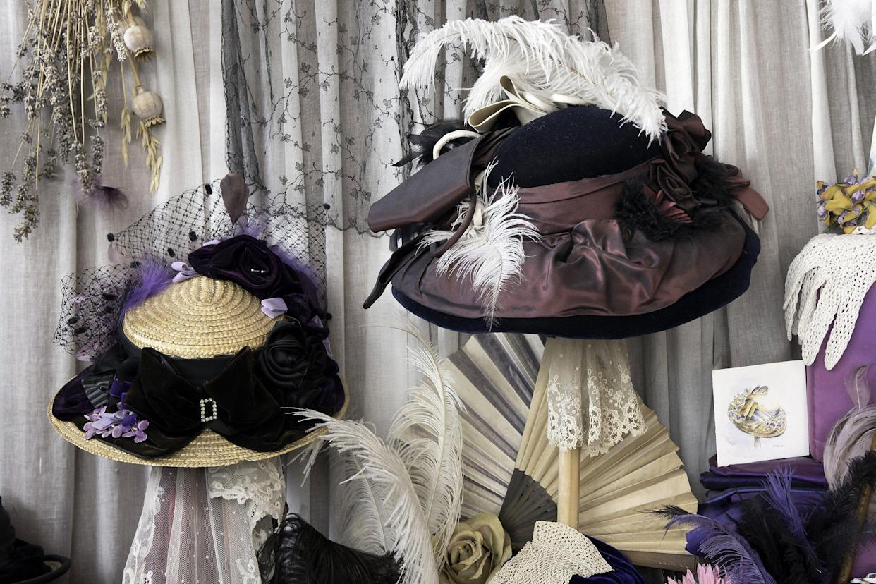 A Victorian hat shop window with feather hats on display