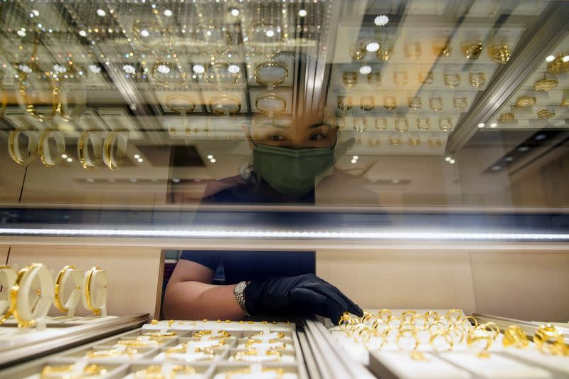 A salesperson poses with gold jewellery at jeweller Chow Tai Fook's retail store in Shanghai