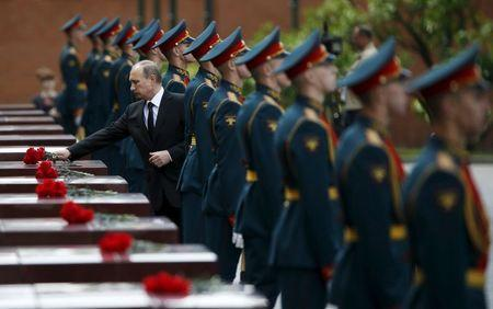 Russia's President Vladimir Putin lays flowers during a ceremony to commemorate the anniversary of the beginning of the Great Patriotic War against Nazi Germany in 1941 near memorials by the Kremlin walls in Moscow, in this June 22, 2014 file photo. REUTERS/Maxim Zmeyev/Files