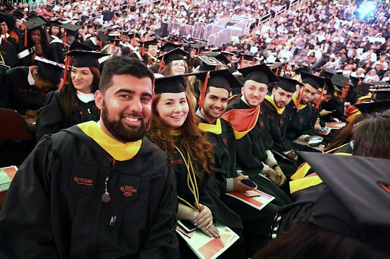 College graduates sit in chairs at a commencement ceremony.