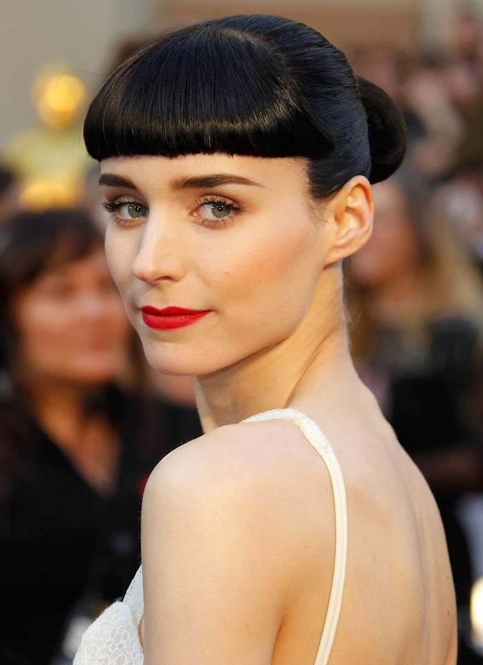 <p>Actress Rooney Mara's high-shine black updo featured straight-across bangs and a tight bun at the 2012 show. Notice how her dark hair looked extra sophisticated against her sheer white dress.</p>