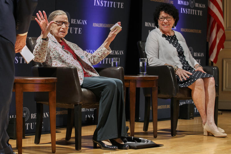 FILE - In this Sept. 25, 2019 file photo, Supreme Court Justice Ruth Bader Ginsburg, left, holds up her hands as she and Supreme Court Justice Sonia Sotomayor arrive to applause for a panel discussion celebrating Sandra Day O'Connor, the first woman to be a Supreme Court Justice, at the Library of Congress in Washington. A month before the Supreme Court takes up cases over his tax returns and financial records, President Donald Trump on Tuesday made the unusual suggestion that two liberal justices should not take part in those or any other cases involving him or his administration. The remarks critical of Justices Ruth Bader Ginsburg and Sonia Sotomayor came during a news conference in India, where Trump was wrapping up a 36-hour visit.   (AP Photo/Jacquelyn Martin)