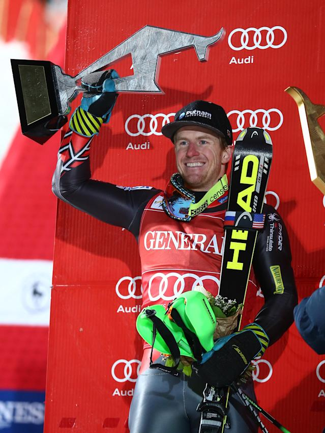 Ted Ligety, of the US, holds up his trophy on the podium after taking second place in an alpine ski men's World Cup super-combined in Kitzbuehel, Austria, Sunday, Jan. 26, 2014. (AP Photo/Giovanni Auletta)