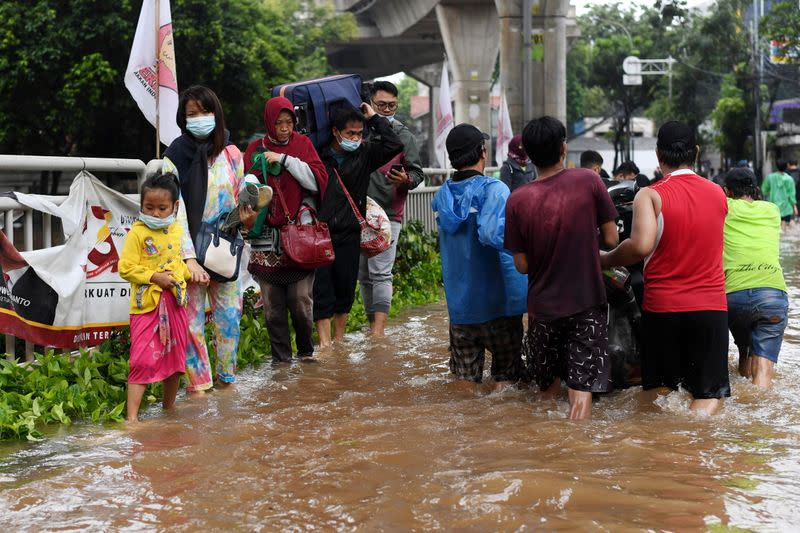 People walk through the water in an area affected by floods following heavy rains in Jakarta