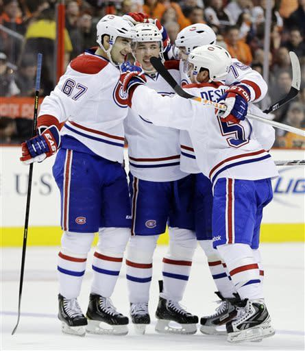 Montreal Canadiens' Max Pacioretty (67), Alexei Emelin (74), of Russia, Andrei Markov (79), also of Russia, and David Desharnais celebrate after a goal by Emelin during the first period of an NHL hockey game against the Philadelphia Flyers, Wednesday, April 3, 2013, in Philadelphia. (AP Photo/Matt Slocum)