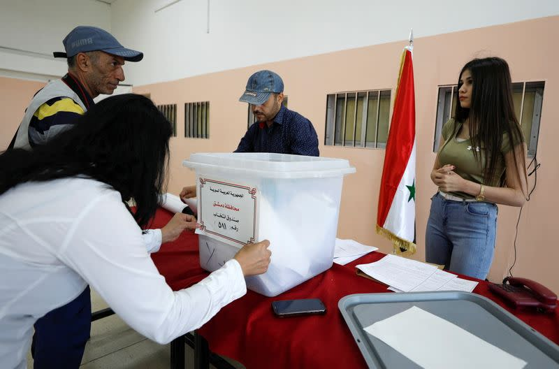 A woman prepares a ballot box during the presidential elections at a polling centre in Damascus
