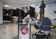 A woman with a child casts a ballot at a polling station during the second round of a parliamentary election in Vilnius, Lithuania, Sunday, Oct. 25, 2020. Polls opened Sunday for the run-off of national election in Lithuania, where the vote is expected to bring about a change of government following the first round, held on Oct. 11, which gave the three opposition, center-right parties a combined lead. (AP Photo/Mindaugas Kulbis)