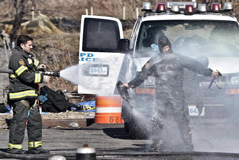 A police diver, fearful of contamination, is sprayed with water from a firefighter, after diving the Steinway Creek to recover a 2009 Honda Accord on Saturday April 5, 2014 in New York. The driver of the car drove off a dead-end street in a desolate industrial area, flipped over a wooden curb into the East River inlet killing four passengers. The driver escaped serious injury and told officers at the scene in the Astoria section of Queens that the four were trapped in the submerged car. Fire department divers pulled the four victims from the car. Police identified them as 21-year-old Darius Fletcher, 19-year-old Jada Monique Butts, 19-year-old Crystal Gravely and 20-year-old Jaleel Furtado. They were pronounced dead at hospitals. (AP Photo/Bebeto Matthews)