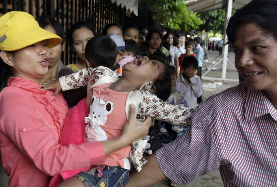 A girl cries while villagers line up to wait for a medical check-up for children outside Kuntha Bopha children's hospital in Phnom Penh, Cambodia, Wednesday, July 11, 2012. The enterovirus 71 strain, or EV-71, raised fears earlier this week after it was detected in some lab samples taken after 52 of 59 Cambodian children died suddenly from a mystery illness that sparked international alarm. Health officials are still investigating, but say the virus is likely to blame. (AP Photo/Heng Sinith)